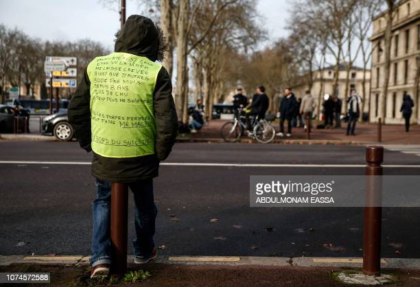 A protester wearing a 'Yellow Vest' reading ' Handicapped at 65% without being seen the MDPH let me die and also others making 500 euro/per month...