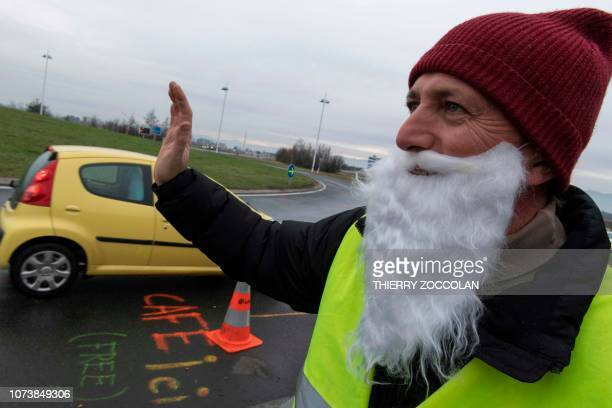 """Protester wearing a yellow vest sporting a Santa Claus beard waves to drivers as Yellow Vests occupy the """"rond-point des Gaulois"""" during a protest..."""