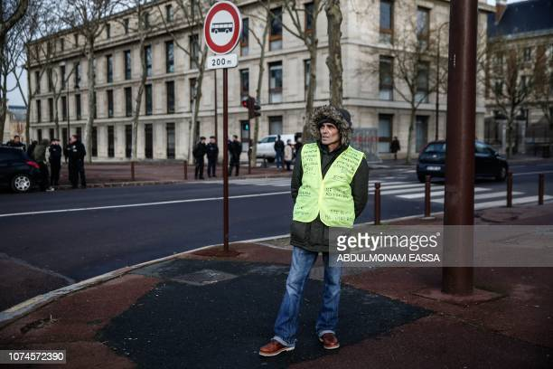 A protester wearing a 'Yellow Vest' stands in a street next to police officers near the Chateau de Versailles in Versailles outside Paris on December...