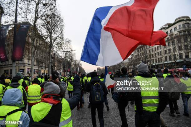 TOPSHOT A protester wearing a yellow vest waves a French national flag during a demonstration on the Champs Elysees Avenue by the Arc de Triomphe in...