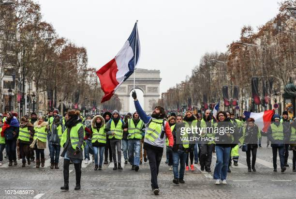 TOPSHOT A protester wearing a yellow vest waves the French national flag during a demonstration against rising costs of living blamed on high taxes...