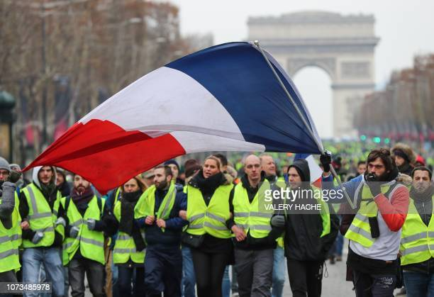 A protester wearing a yellow vest waves the French national flag during a demonstration against rising costs of living blamed on high taxes on the...