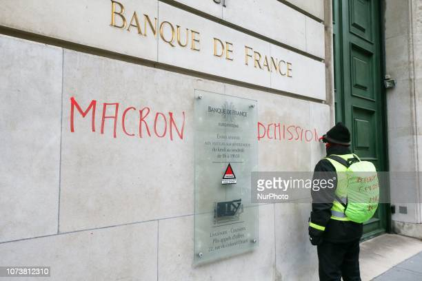A protester wearing a yellow vest writes « Macron resignation » on the wall of the Banque de France during a demonstration against rising costs of...
