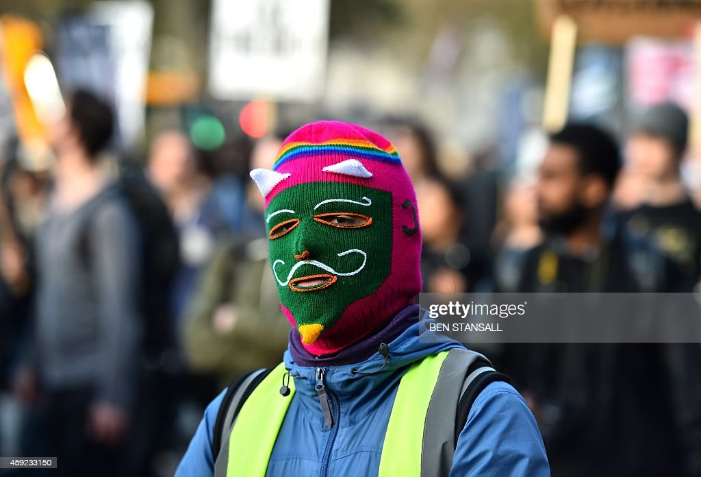 A protester wearing an anonymous balakcava takes part in a march in London against university fees on November 19, 2014. The demonstration organised by the Student Assembly Against Austerity, alongside the Young Greens and National Campaign Against Fees and Cuts demands free education and an end to tuition fees, education cuts and student debt.
