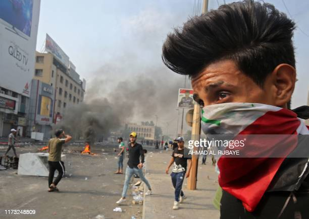 TOPSHOT A protester wearing an Iraqi national flag as a bandana face mask stands during clashes between protesters and riot police amidst...