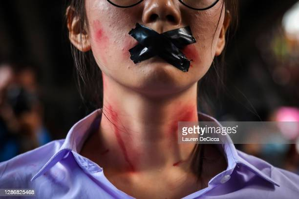 Protester wearing make-up and tape over her mouth poses in the Siam area on November 21, 2020 in Bangkok, Thailand. Pro-democracy protesters kept up...