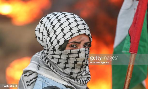 "Protester wearing Palestinian keffiyeh carries a Palestinian flag, on the 24th Friday of ""Great March of Return"" demonstration near Israel-Gaza..."