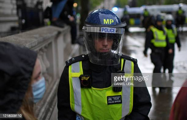 A protester wearing PPE including a face mask as a precautionary measure against COVID19 stands by Police offices in riot gear as they stand on duty...