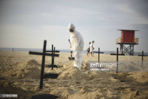 Protester, wearing protective gear, digs a mock grave on Copacabana beach symbolizing deaths due to the coronavirus and protest against governments...