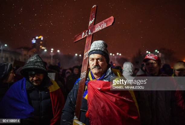 """Protester wearing Romanian flag holds a wooden cross reading """"PSD Mafia"""" during a protest against the Justice minister and the corruption in front of..."""