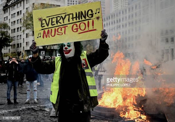 Protester wearing the DC comic Joker character's make up holds a banner on place d'Italie in Paris on November 16 during clashes on the sidelines of...