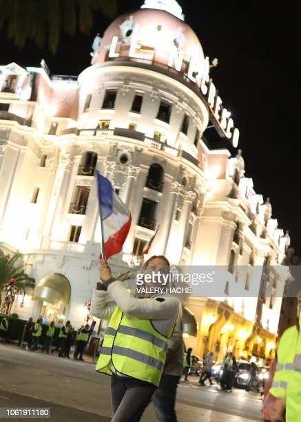 A protester wearing yellow jackets waves a French flag during a protest against the rising of the fuel and oil prices gather in front of the Negresco...