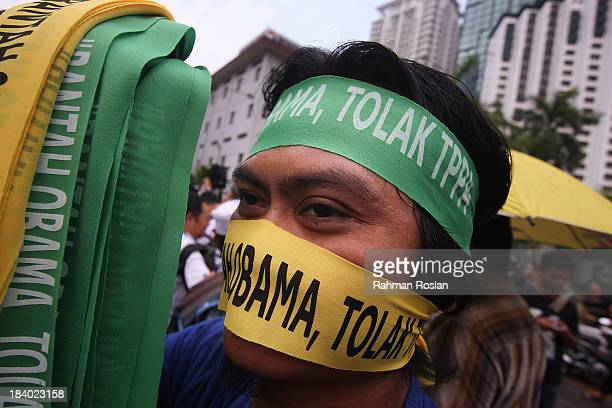 A protester wears a bandana that reads 'Reject Obama' during a protest against Trans Pacific Partnership Agreement outside the Global...