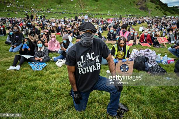 """Protester wears a """"Black Power"""" t-shirt and a face mask during a Black Lives Matter protest in Holyrood Park, despite a call by First Minister,..."""