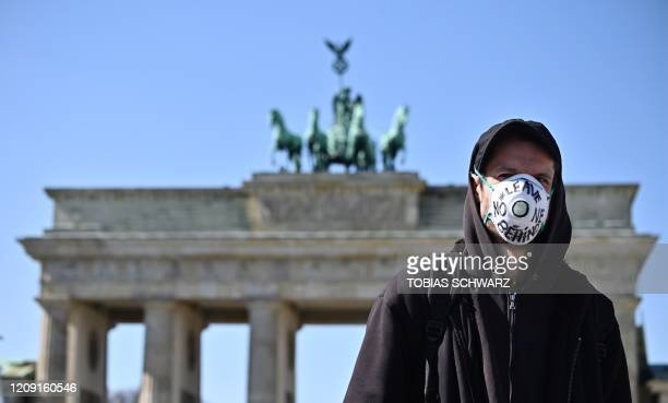 """Protester, wears a face mask bearing the words """"leave no one behind, during a nationwide action under the moto Wir hinterlassen Spuren -..."""