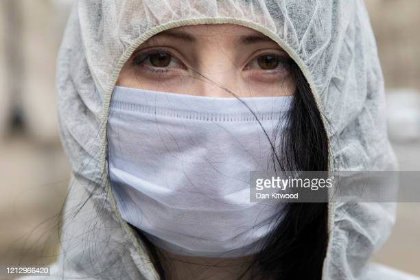 A protester wears a face mask outside Downing Street after the weekly cabinet meeting on March 17 2020 in London England Boris Johnson held the first...