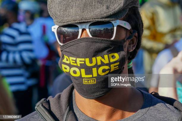Protester wears a face mask written on Defund Police during a Black Trans Lives Matter rally in Hudson River Park.