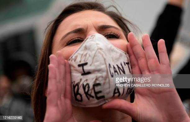 A protester wears a facemask reading I can't breathe as protesters march to the White House in Washington DC on May 29 2020 during a demonstration...