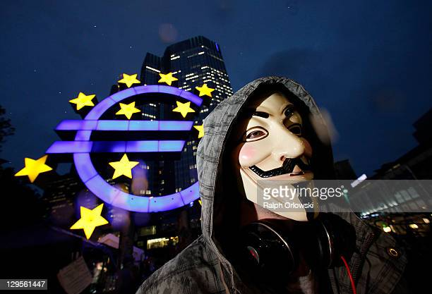 Protester wears a Guy Fawkes masks while demonstrating, inspired by the Occupy Wall Street protests in the United States, in front of the...