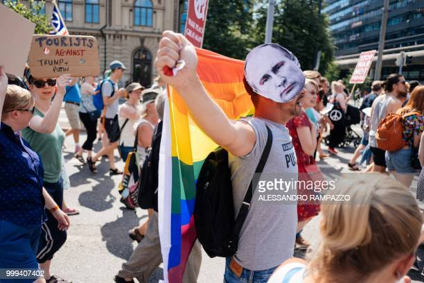 A protester wears a mask bearing a portrait of Russian President Vladimir Putin during the socalled 'Helsinki Calling' march towards the Senate...