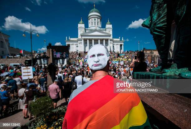 TOPSHOT A protester wears a mask bearing a portrait of Russian President Vladimir Putin as protesters gather on the Senate Square at the end of the...