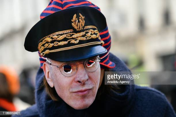 Protester wears a mask depicting a police during a protest against President Emmanuel Macron's controversial pension plans in Paris, France on...