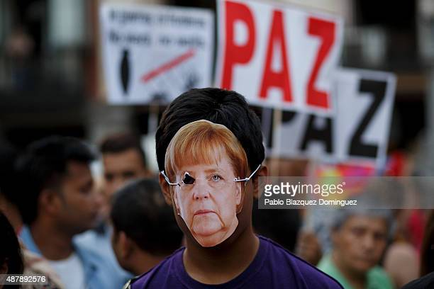 A protester wears a mask depicting 'German Chancellor Angela Merkel' as placards behind read 'Peace' during a demonstration to show solidarity and...