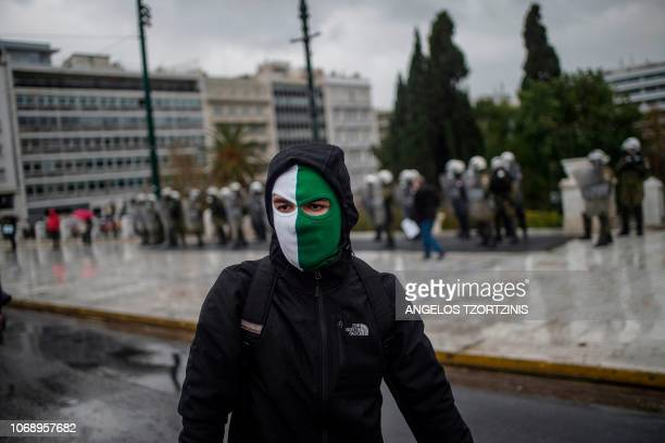 A protester wears a mask during a demonstration in Athens on December 6 2018 to commemorate the 10th anniversary of fatal shooting of a teenager...