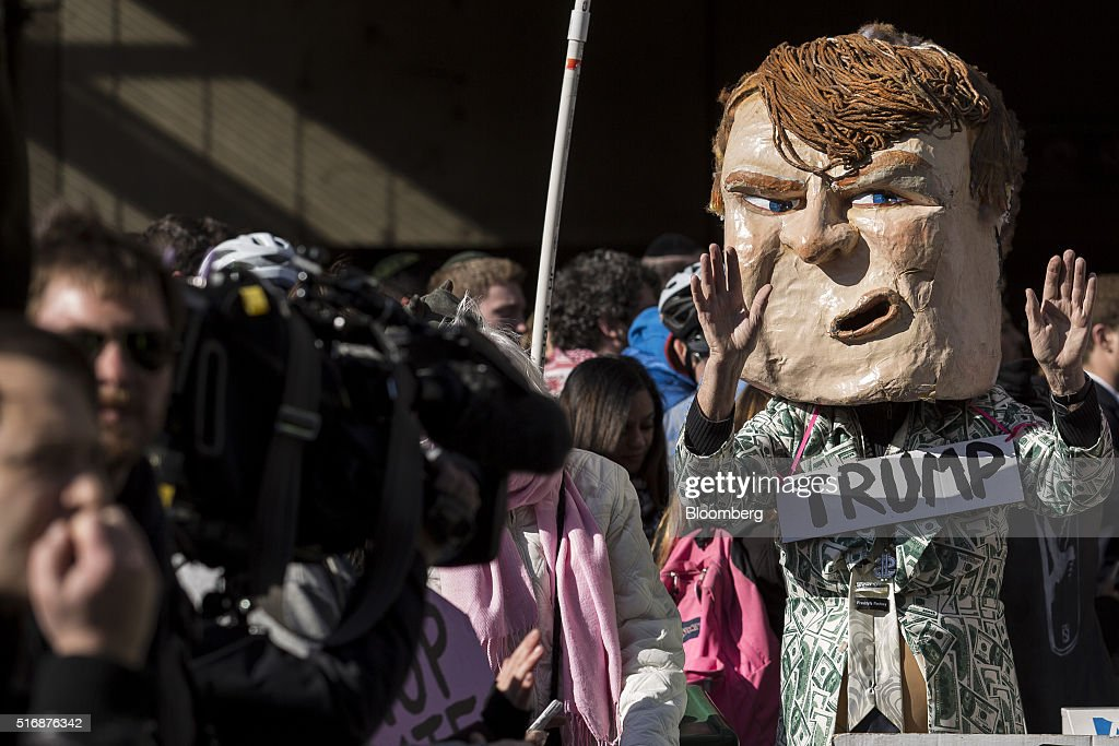 A protester wears a mask in the likeness of Donald Trump, president and chief executive of Trump Organization Inc. and 2016 Republican presidential candidate, outside the American Israeli Public Affairs Committee (AIPAC) policy conference in Washington, D.C., U.S., on Monday, March 21, 2016. The presidential race will take a detour from domestic sniping today as Hillary Clinton, Donald Trump and Trump's two Republican opponents converge on Washington to address a key pro-Israel group. Photographer: Drew Angerer/Bloomberg via Getty Images
