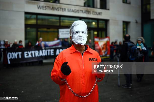 Protester wears a mask of Wikileaks founder Julian Assange and prison overalls as he poses outside Westminster Magistrates Court in London on...