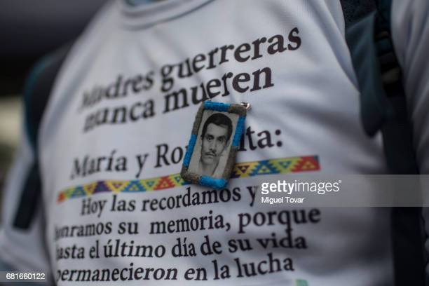 A protester wears a pin with the portrait of his missing relative during a march on Mother's Day on May 10 2017 in Mexico City Mexico Mothers whose...