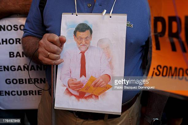 A protester wears a placard depicting Spanish Prime Minister Mariano Rajoy after the arrival of the PP General Secretary Maria Dolores de Cospedal at...