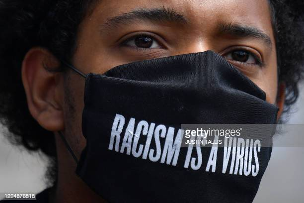 A protester wears a protective face covering with the slogan Racism is a Virus written on the fabric as he listens to speeches at a gathering in...