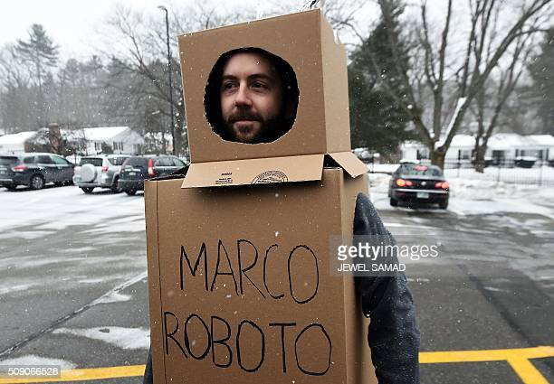 A protester wears a 'robot suit' made out of cardboard as US Republican presidential candidate Marco Rubio arrives at a restaurant for a campaign...