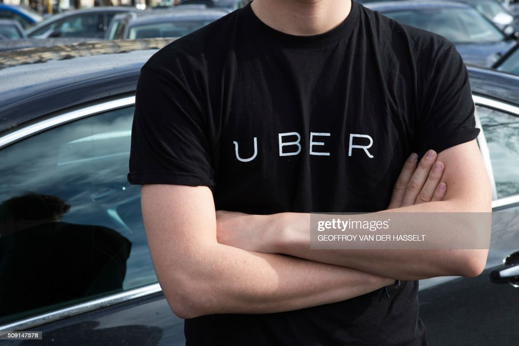 A protester wears a shirt displaying the logo of smartphone ride service Uber during by a protest by non-licensed private hire drivers blocking the Place de la Nation in Paris on February 9, 2016. ...