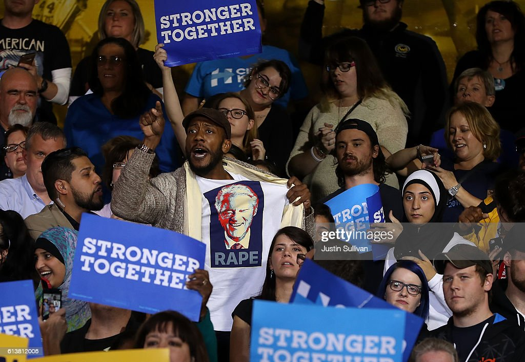 A protester wears a shirt with an image of former U.S. president Bill Clinton and the word 'rape' as democratic presidential nominee former Secretary of State Hillary Clinton speaks during a campaign rally at Wayne State University on October 10, 2016 in Detroit, Michigan. A day after the second presidential debate in St. Louis, Hillary Clinton is campaigning in Michigan and Ohio.