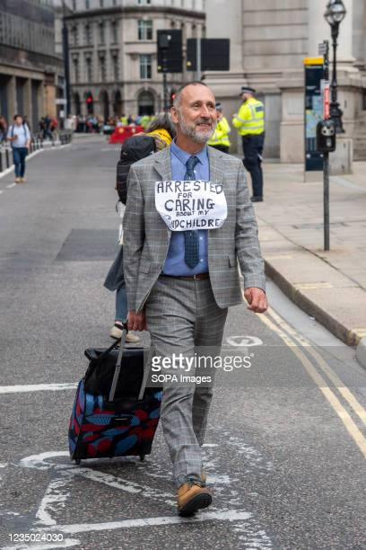 Protester wears a sign saying Arrested for caring about my grandchildren during the demonstration. Extinction Rebellion Impossible Rebellion on day...