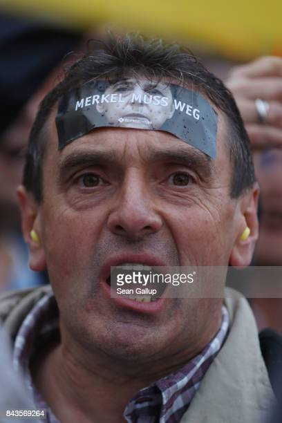 A protester wears a sticker on his forehead that reads Merkel muss weg at the edge of an election campaign stop where German Chancellor and Christian...