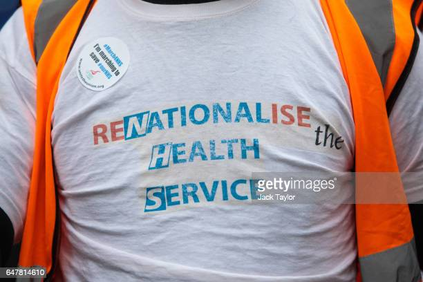 A protester wears a tshirt which says 'Renationalise the Heath Service' during a march through central London in support of the NHS on March 4 2017...