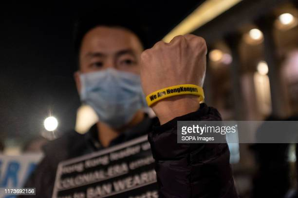 A protester wears a wrist band that says We are Hongkongers while holding a placard during the demonstration Protesters rallied at Trafalgar Square...