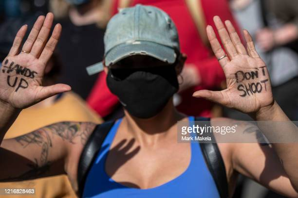 """Protester wears body paint on her hands stating """"HANDS UP"""" """"DON'T SHOOT"""" during a march through Center City on June 1, 2020 in Philadelphia,..."""