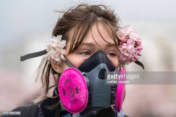 Protester wears cherry blossoms and a gas mask at a counter demonstration to a planned far-right rally on March 28, 2021 in Salem, Oregon. The...