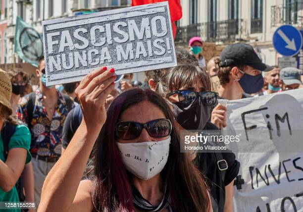 """Protester wears her protective mask as she holds a """"Fascism Never More"""" sign during a rally to demonstrate against Fascism, Nazism and racism on July..."""
