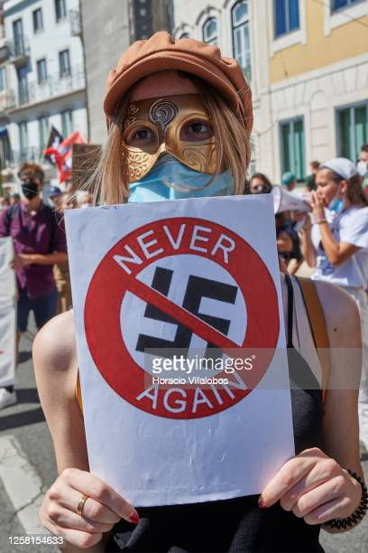 Protester wears her protective mask as she holds an anti nazi sign during a rally to demonstrate against Fascism, Nazism and racism on July 25, 2020...