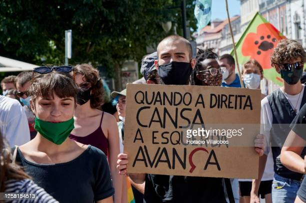 """Protester wears his protective mask as he holds a """"When the Right tires the Left moves forward"""" sign during a rally to demonstrate against Fascism,..."""