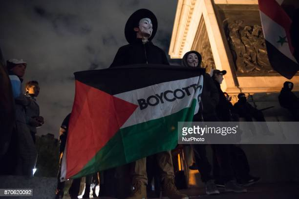 A protester wears the iconic Guy Fawkes mask and waves a Palestine flag in Trafalgar Square during the anticapitalist 'Million Masks March' organised...