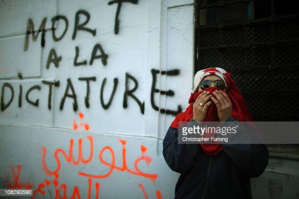 Protester who marched from the rural areas of Tunisia wears a national flag as a headdress outside the prime ministers office on January 23, 2011 in...