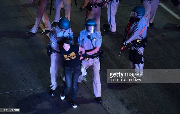 A protester who refused to leave is apprehended by California Highway Patrol officers who moved in to clear protesters off a freeway in downtown Los...