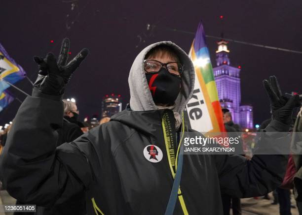 """Protester with a face mask with a lightning bolt on it as a sign of """"Strajk Kobiet"""" attends a demonstration demanding the restoring of the right to..."""