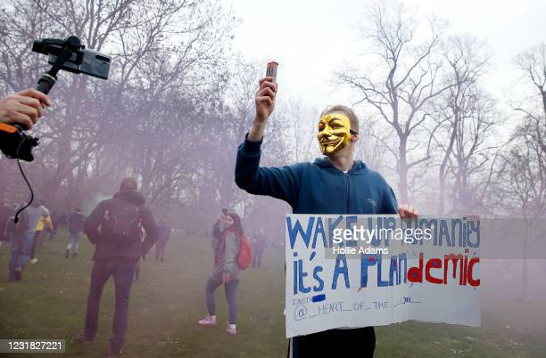 """Protester with a flare poses holding a sign calling for people to """"wake up"""" during a """"World Wide Rally For Freedom"""" protest on March 20, 2021 in..."""
